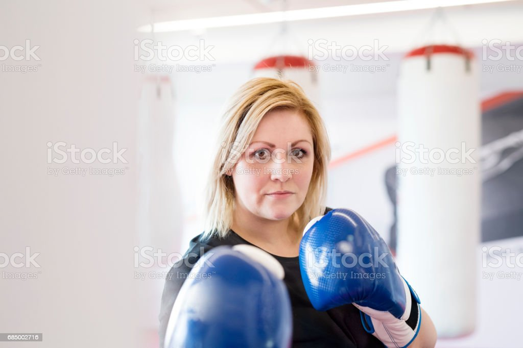 Attractive overweight woman in gym with boxing gloves on. stock photo