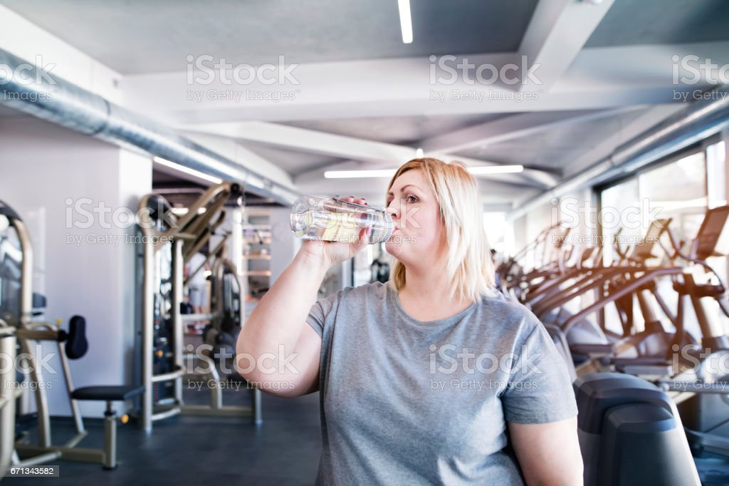 Attractive overweight woman in modern gym resting, drinking water. stock photo