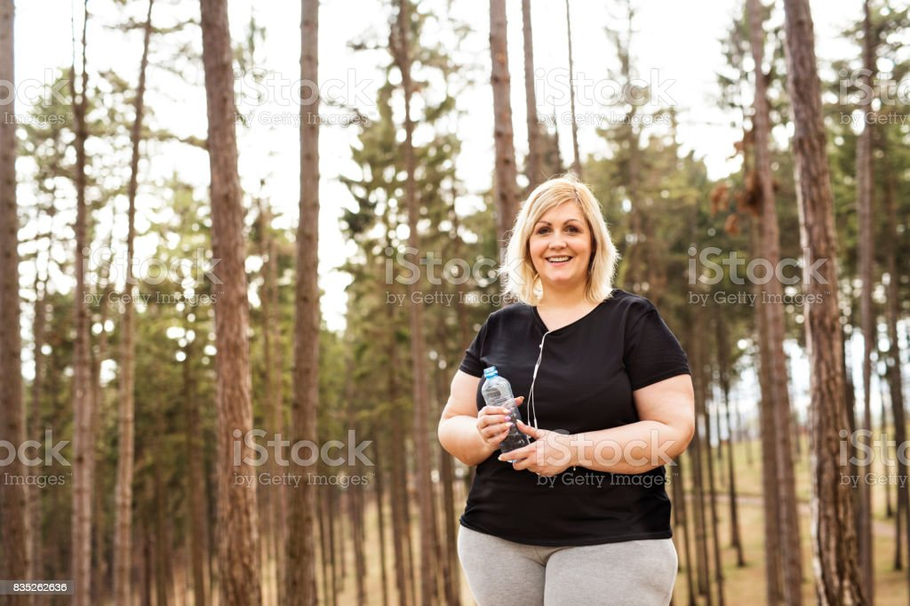 Attractive overweight woman running in park. stock photo