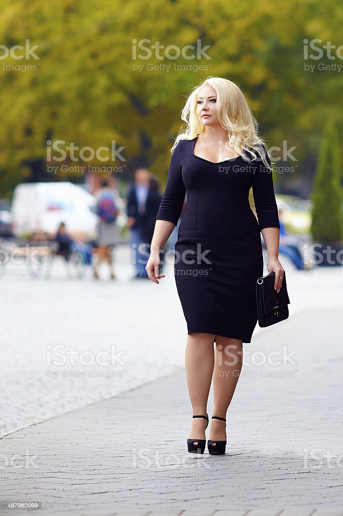 attractive overweight woman walking the city street stock photo