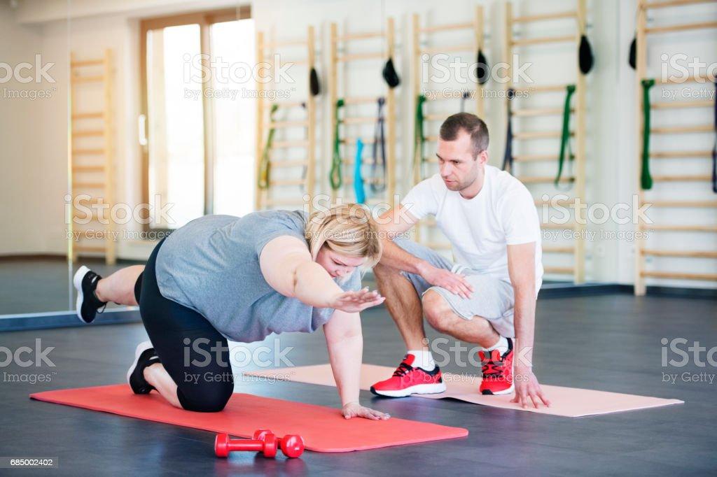Attraktive übergewichtige Frau mit ihrem persönlichen Trainer im modernen Fitnessraum trainieren auf Matte Lizenzfreies stock-foto