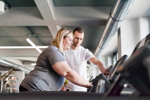 Attractive overweight woman with her personal trainer running on treadmill in modern gym. stock photo