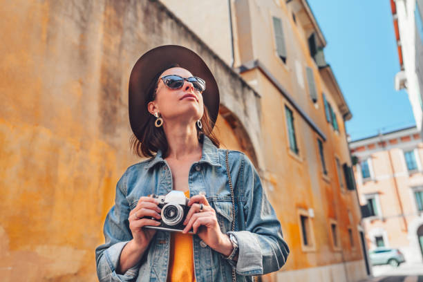 Attractive photographer with a retro camera outdoors