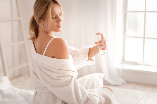 attractive pleasant woman using body spray - spruzzo profumo foto e immagini stock