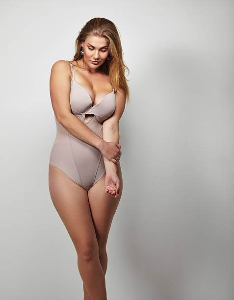 attractive plus size young lady in body stocking - curvy voluptuous women stock photos and pictures