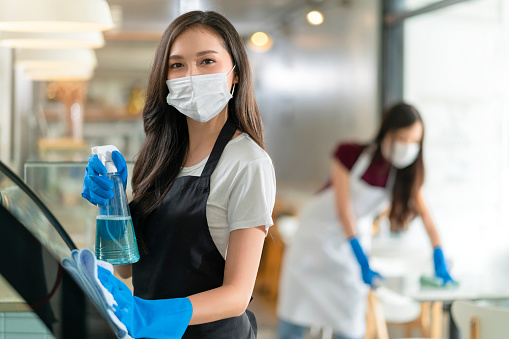 attractive positive young Asian woman staff in uniform apron spraying detergent or alcohol on counter product cabinet  wiping it with soft cloth when disinfecting cafe in ther morning safe and clean