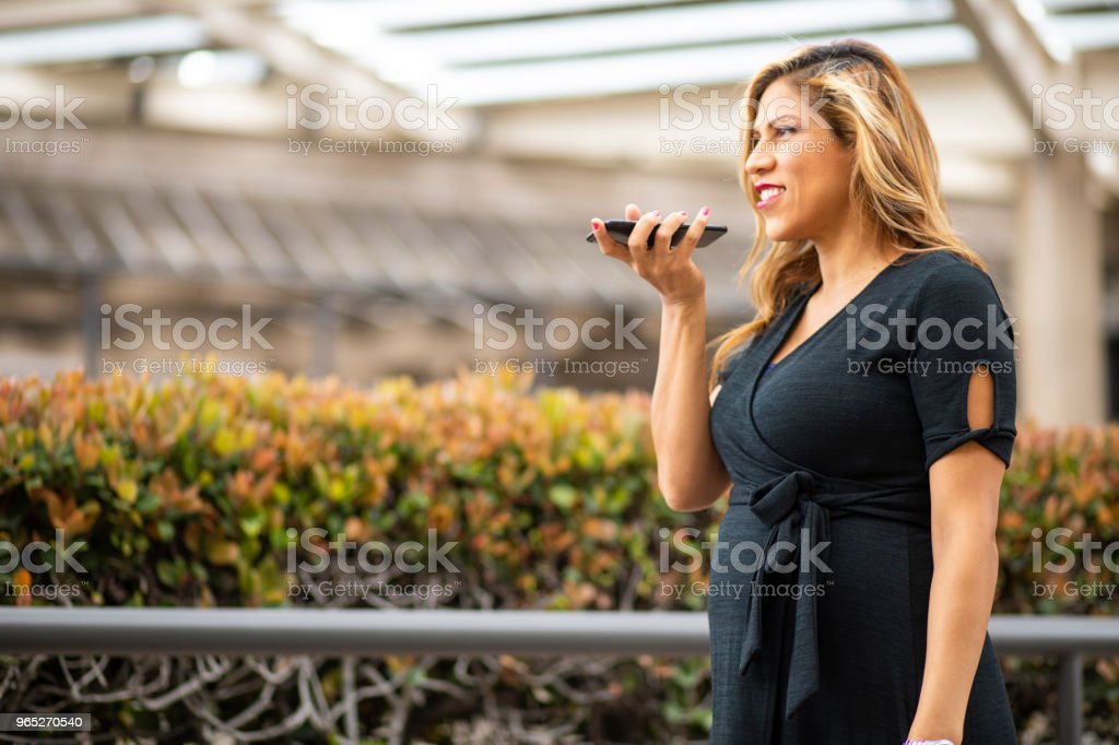 Attractive Pregnant Hispanic Businesswoman using Smartphone royalty-free stock photo