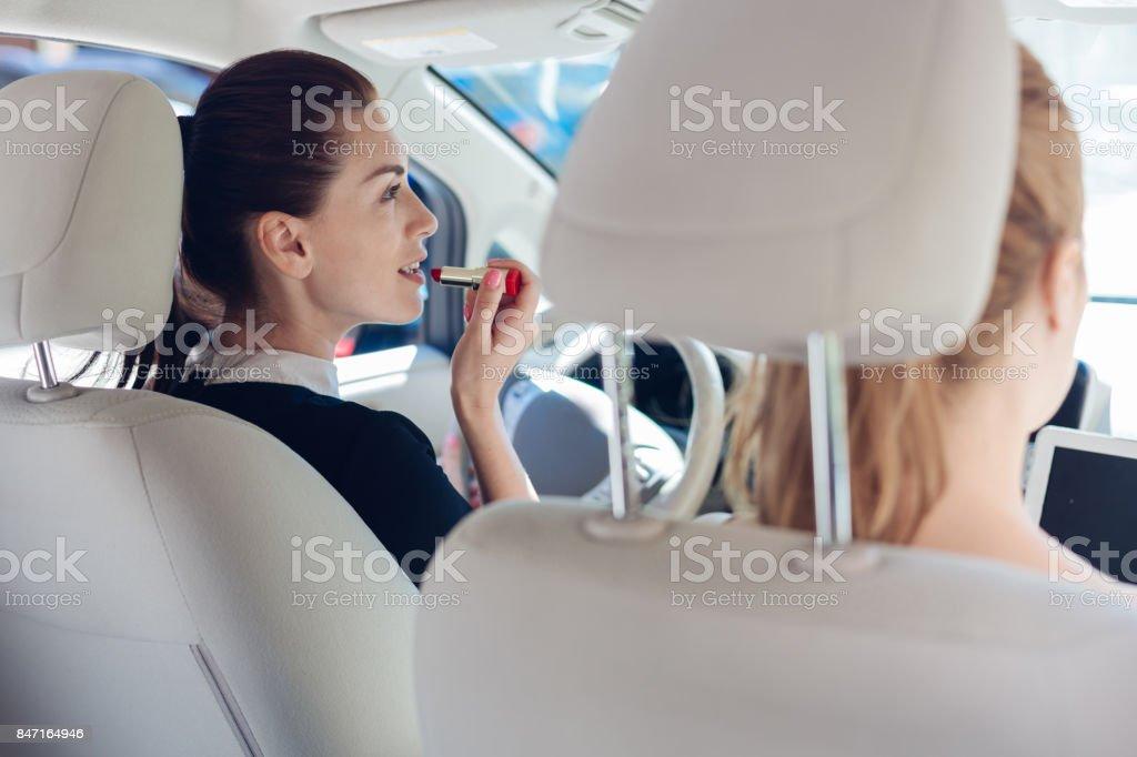 Attractive pretty woman using a lipstick stock photo