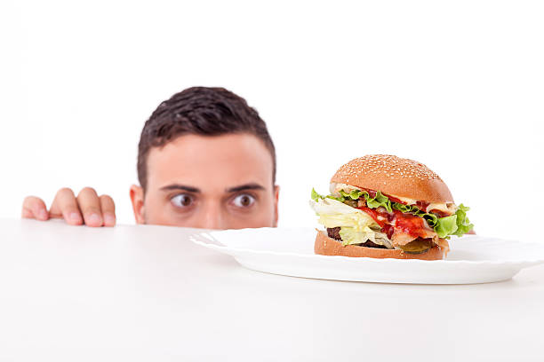 Attractive pretty young man is very hungry Cheerful guy is hiding behind a table and peeping through it. He is looking at an unhealthy hamburger with desire. Isolated on background temptation stock pictures, royalty-free photos & images