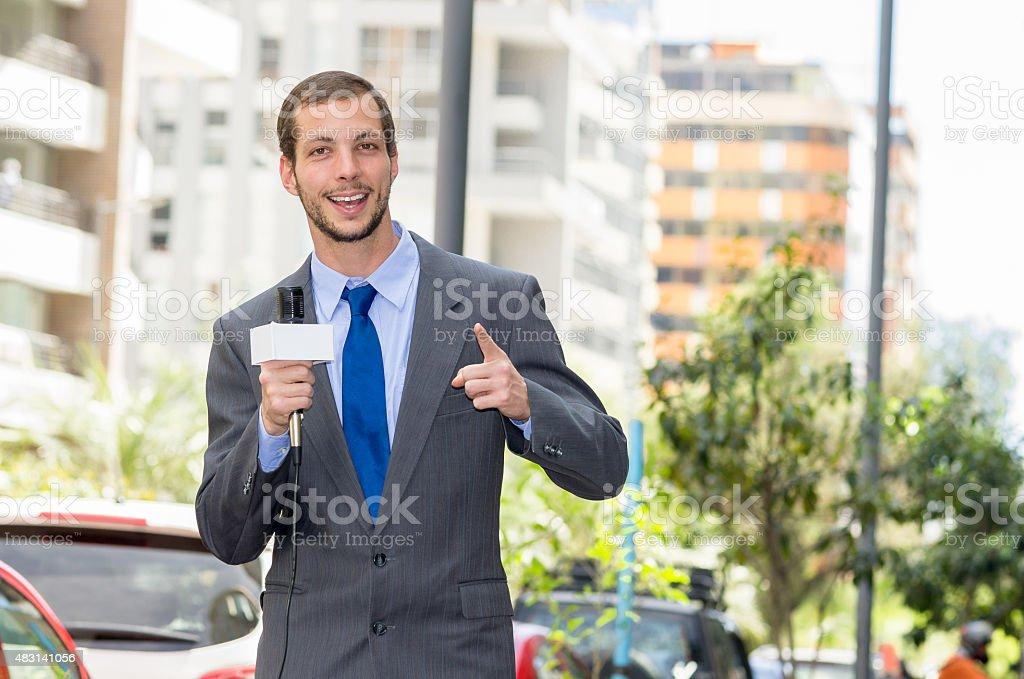 Profissional masculino atraente vestindo cinza terno notícias repórter segurando um microfone - foto de acervo