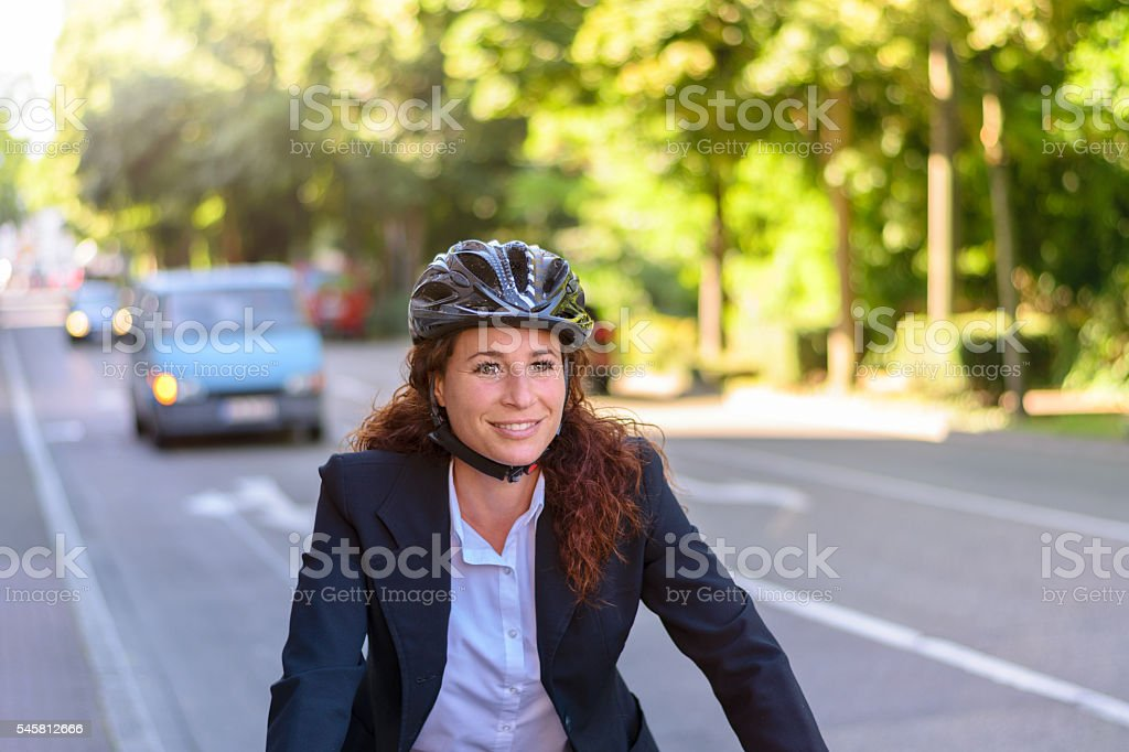 Attractive professional woman cycling to work stock photo