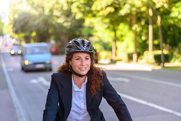 attractive professional woman cycling to work - hauptverkehrszeit stock-fotos und bilder