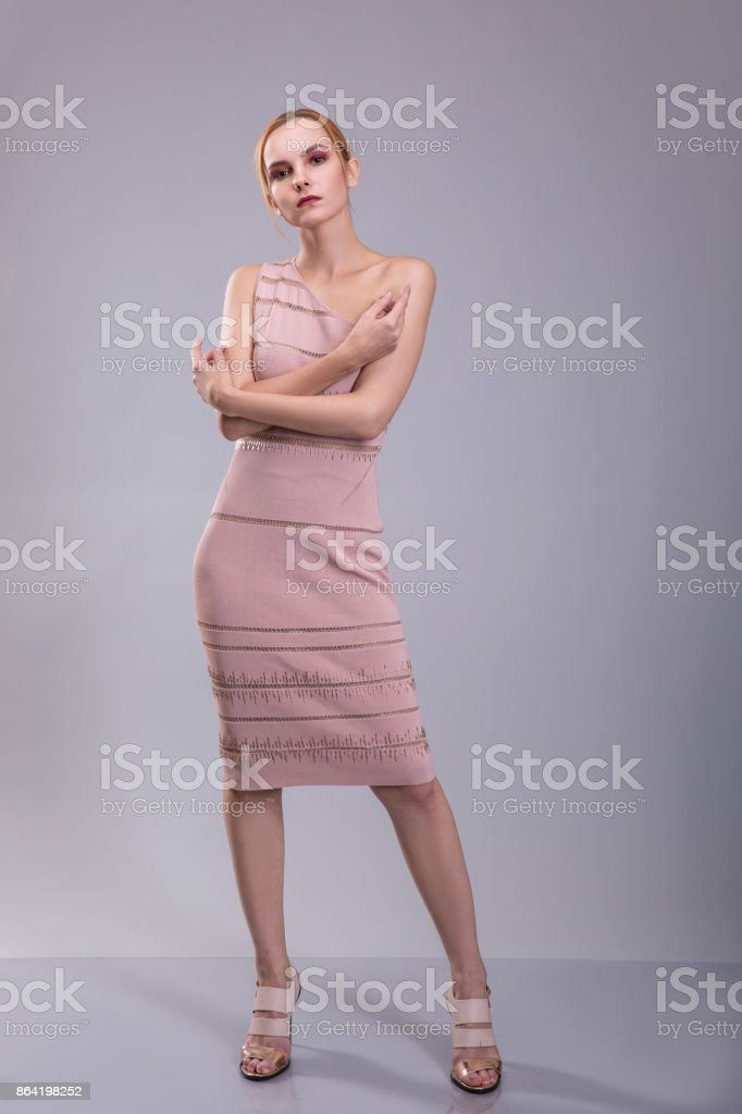 Attractive red head woman posing in light dress on grey background royalty-free stock photo