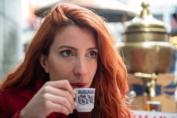 Attractive red woman drinking coffee stock photo
