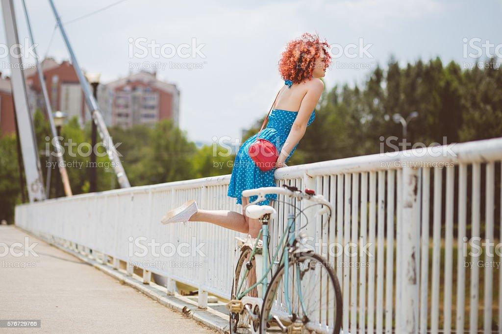 Attractive  redhead on the bridge stock photo