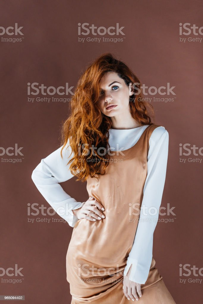 Attractive redhead woman in beige dress isolated on brown background royalty-free stock photo
