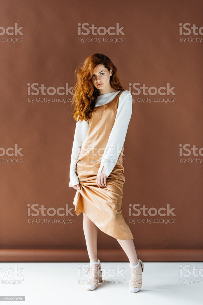 Attractive redhead woman in beige dress posing on brown background zbiór zdjęć royalty-free