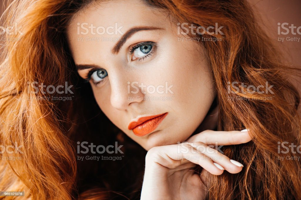 Attractive redhead woman leaning on hand isolated on brown background royalty-free stock photo