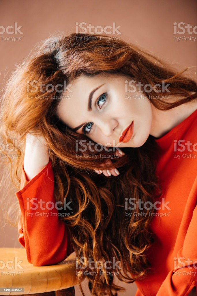 Attractive redhead woman leaning on stool isolated on brown background royalty-free stock photo