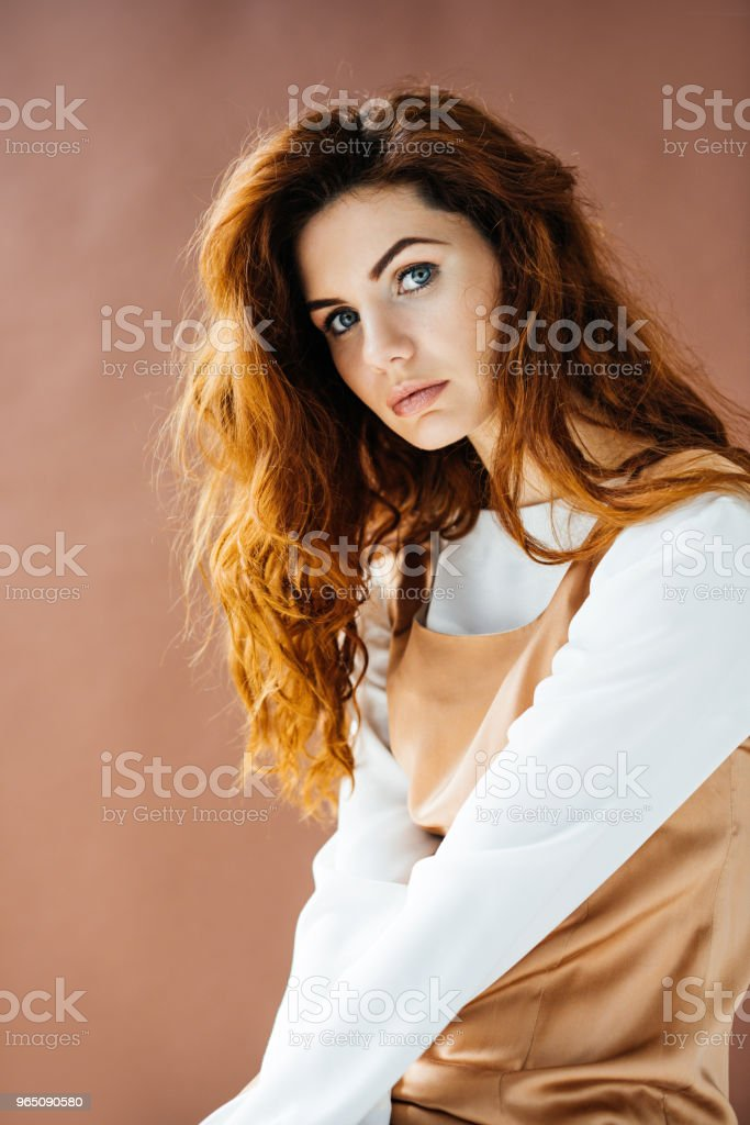 Attractive redhead woman looking at camera isolated on brown background zbiór zdjęć royalty-free