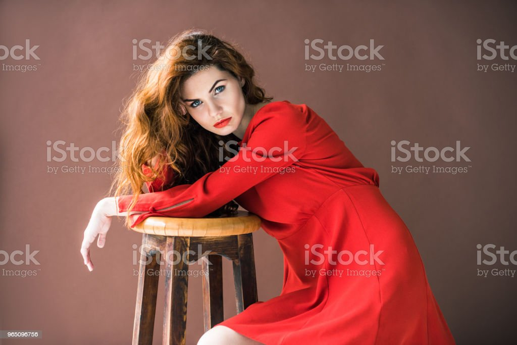 Attractive redhead woman posing by wooden stool isolated on brown background royalty-free stock photo