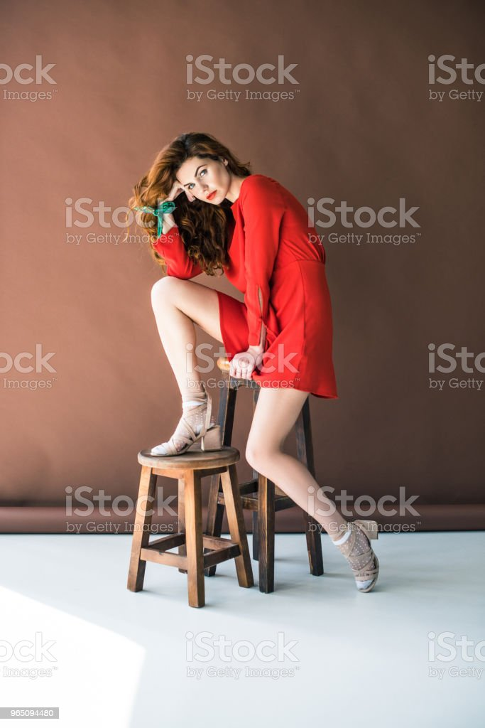 Attractive redhead woman posing on wooden stool zbiór zdjęć royalty-free