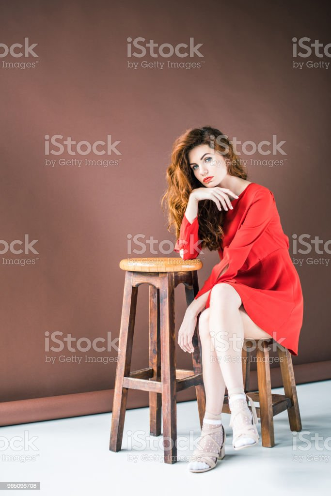 Attractive redhead woman sitting on chair by tall stool royalty-free stock photo