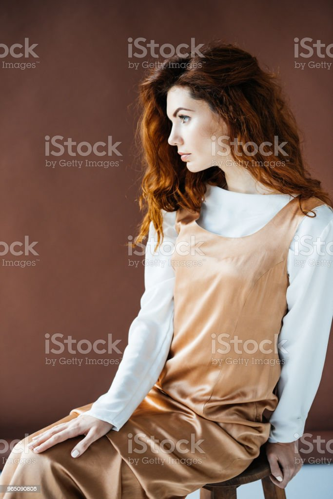 Attractive redhead woman sitting on wooden stool royalty-free stock photo