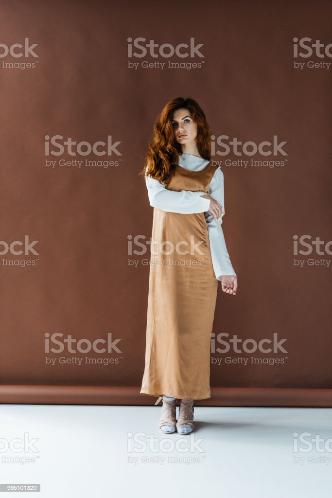 Attractive redhead woman standing on brown background royalty-free stock photo