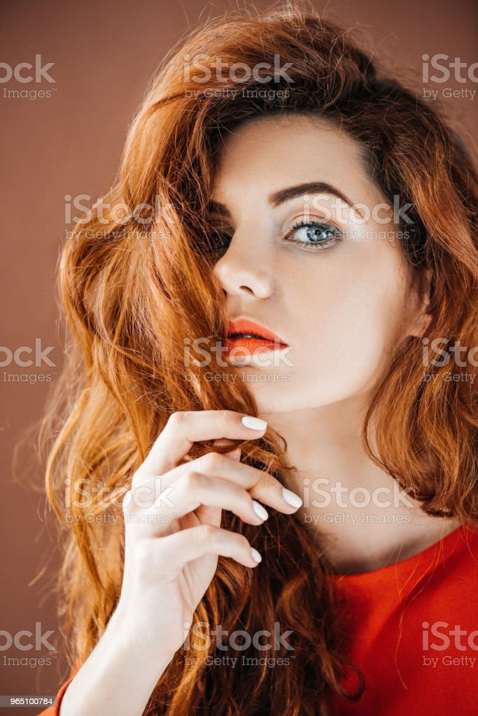 Attractive redhead woman touching hair isolated on brown background royalty-free stock photo
