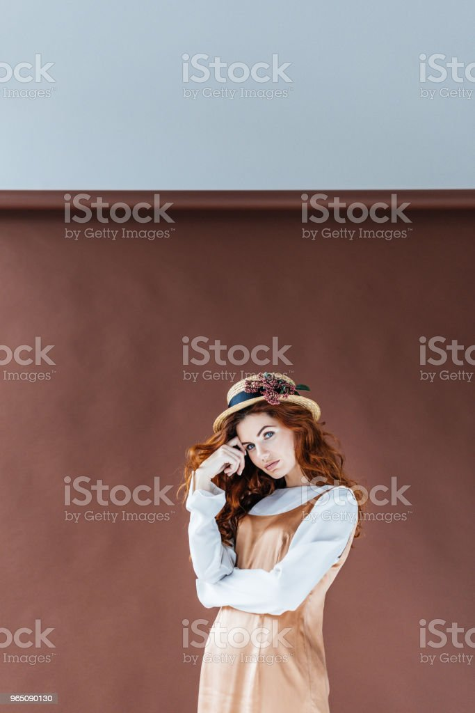 Attractive redhead woman wearing straw hat with flowers royalty-free stock photo