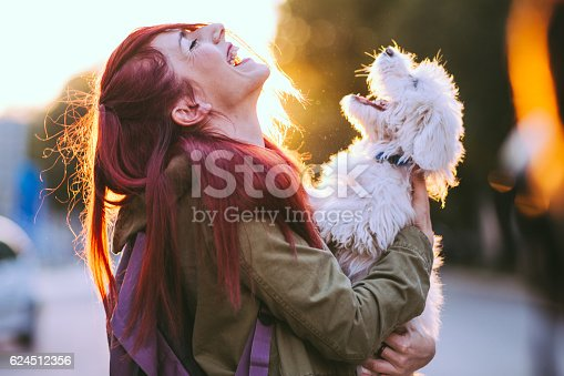 istock Attractive Redheaded Girl and White Puppy Smiling Together 624512356