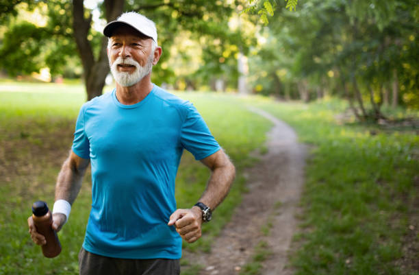 Attractive retired man with a nice smile jogging in park stock photo