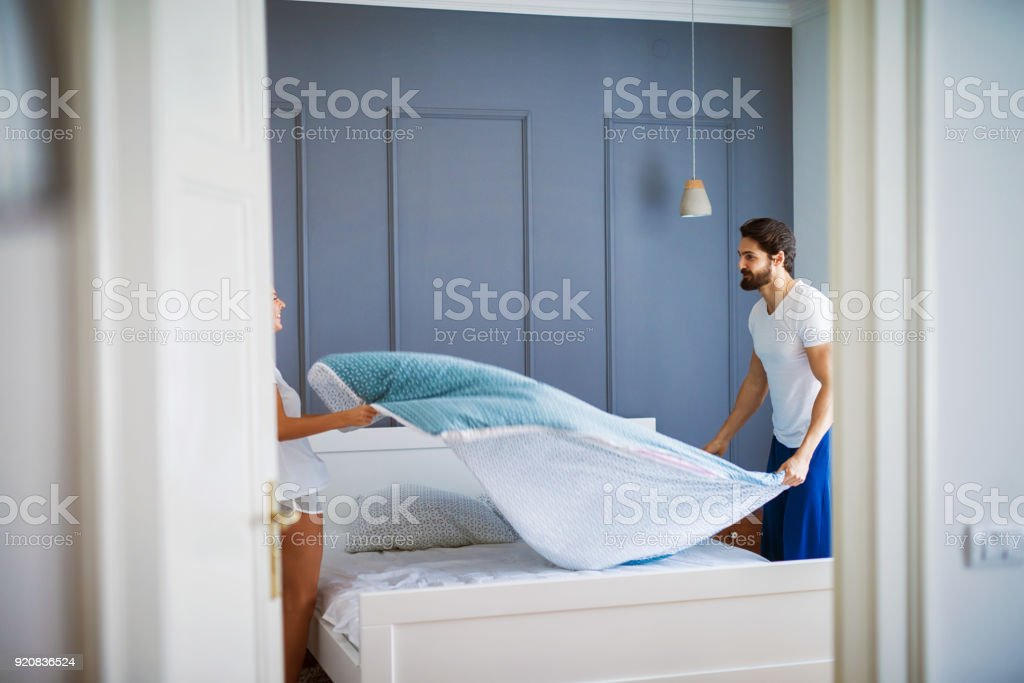 Attractive romantic lovers making the bed together and sharing the feeling of happiness. stock photo