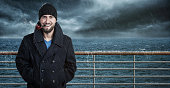 Attractive seafarer on his ship in bad weather