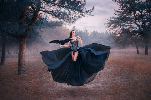 attractive seductive sexy fantasy witch levitating in air. Woman with black raven on hand. wings bird. silk dress flutters. Gothic vintage style design. Cold winter forest nature backdrop with fog