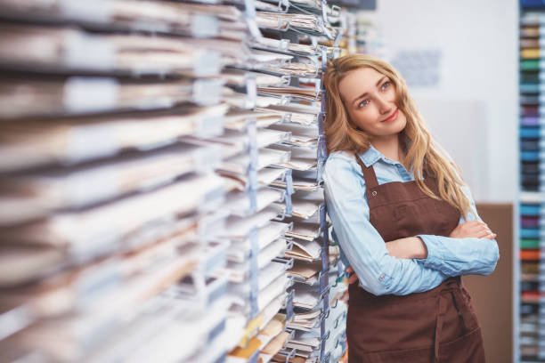 Attractive seller in uniform in the art store stock photo