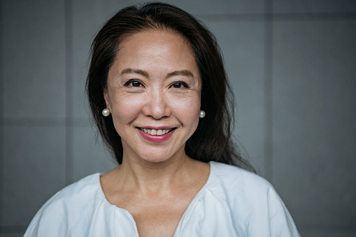 Headshot of businesswoman in her 60s looking at camera, confidence, cheerful, beauty