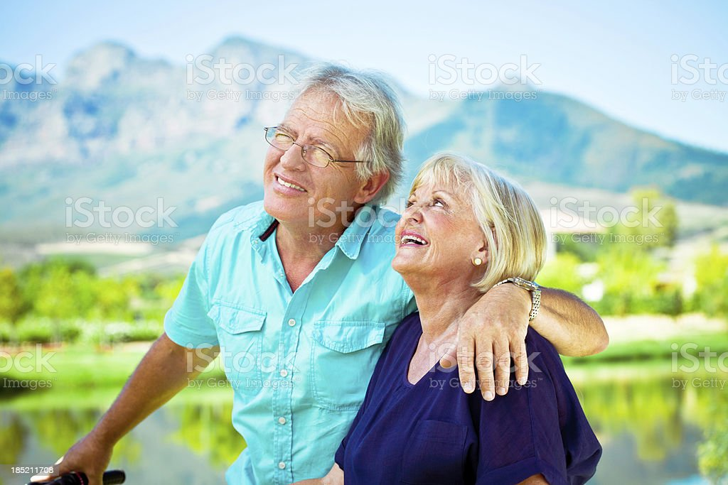 Attractive senior couple Outdoor portrait of happy senior couple embracing with beautiful mountains view in the background. 60-64 Years Stock Photo