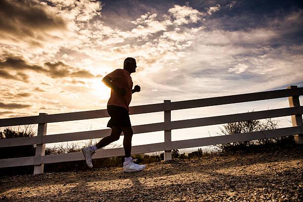 attractive senior man jogging - jogging hill bildbanksfoton och bilder