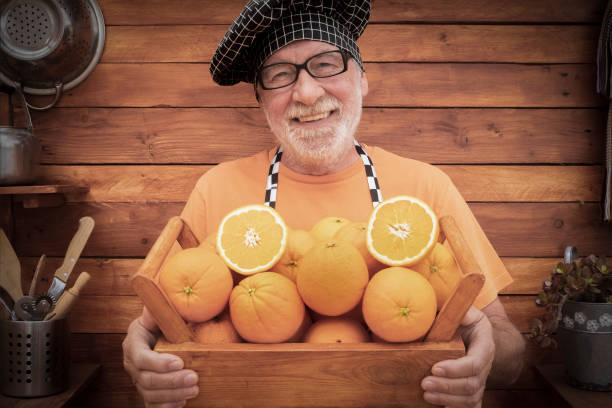 aantrekkelijke hogere mens met een chef-kokglb die mand hoogtepunt van verse sinaasappels - gezond eet en levensstijlconcept - oogst bij km nul houdt - oldman chef's cap hat stockfoto's en -beelden