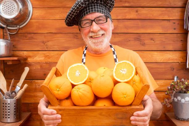 aantrekkelijke hogere mens met een chef-kokglb bekijkt camera en houdt een mand hoogtepunt van sinaasappelen die aan vitaminen rijk zijn. een gezonde levensstijl - oldman chef's cap hat stockfoto's en -beelden