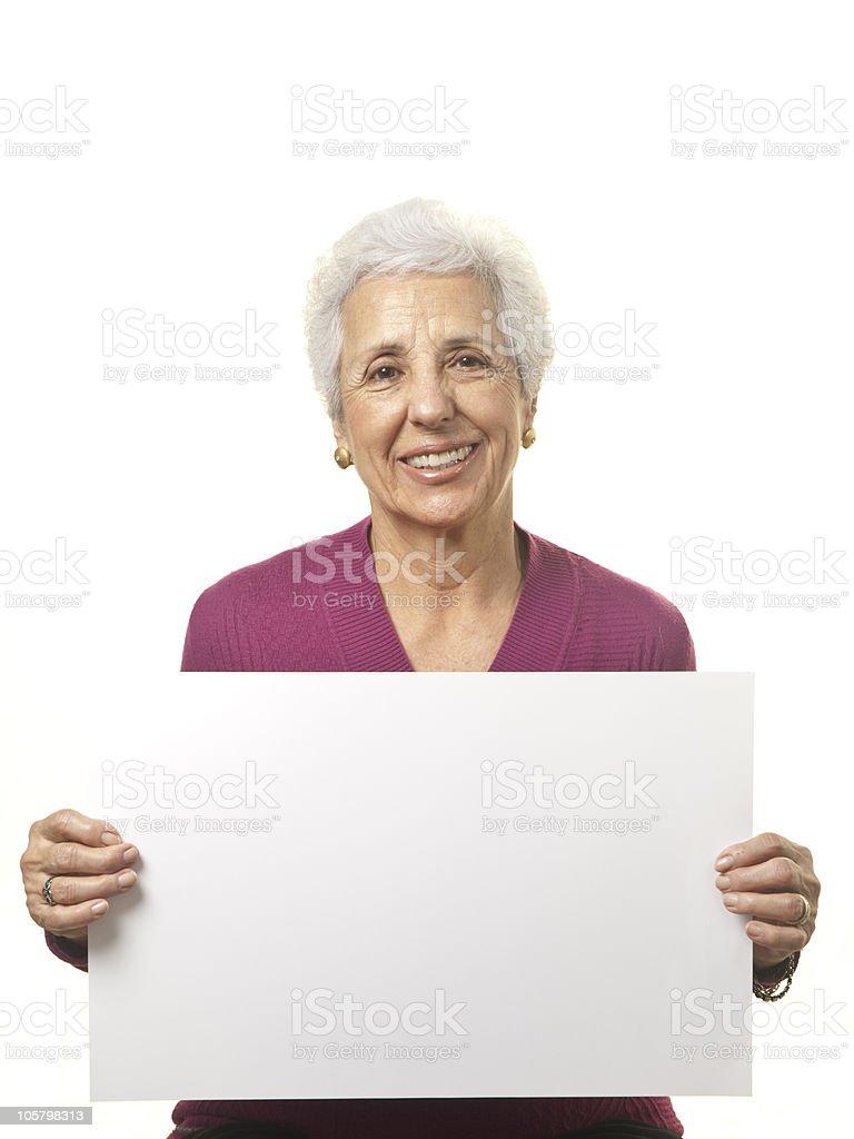 Attractive senior woman holding blank billboard stock photo