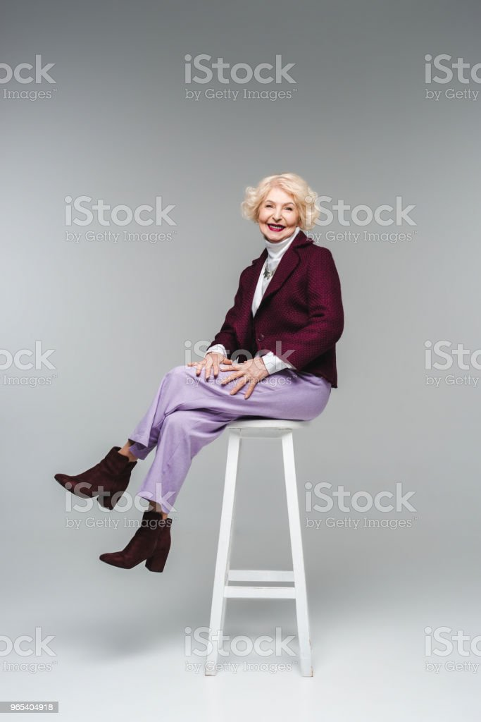 attractive senior woman in stylish clothes sitting on chair on grey royalty-free stock photo
