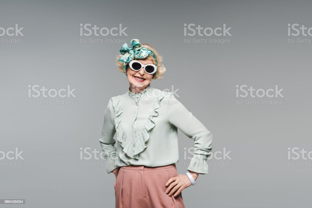 attractive senior woman in stylish headband and sunglasses isolated on grey royalty-free stock photo