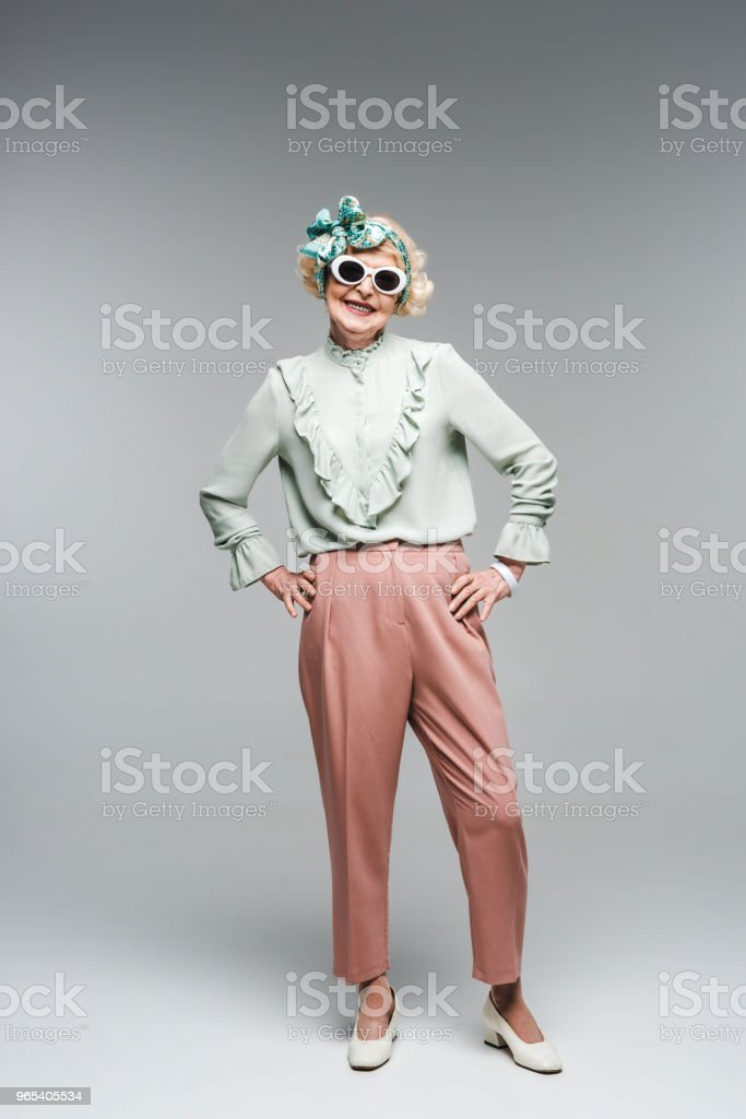 attractive senior woman in stylish headband and sunglasses on grey royalty-free stock photo