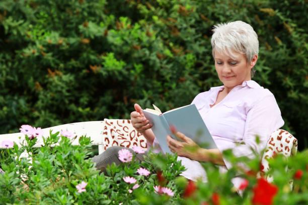 attraktive ältere frau liest ein buch-äußeres - gedichte zum ruhestand stock-fotos und bilder