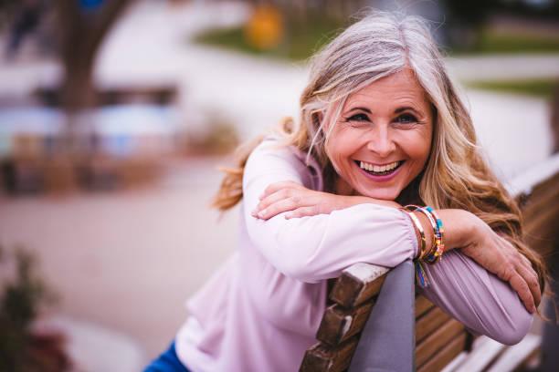 attraktive ältere frau lachend und sitzt auf der parkbank - altes damenhaar stock-fotos und bilder