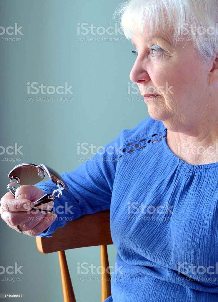 Attractive Senior woman looking pensive, holding sunglasses royalty-free stock photo