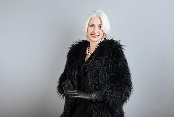 attractive senior woman standing against isolated background. - celebrities of age bildbanksfoton och bilder